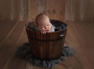 Tiny baby in a blanket in a bucket taken by newborn photographer Glasgow