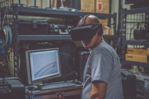 Man testing out VR gaming jobs with headset on in warehouse