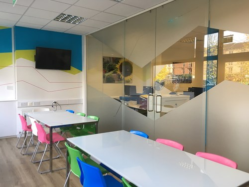 Customised glass office partitions around a meeting room.
