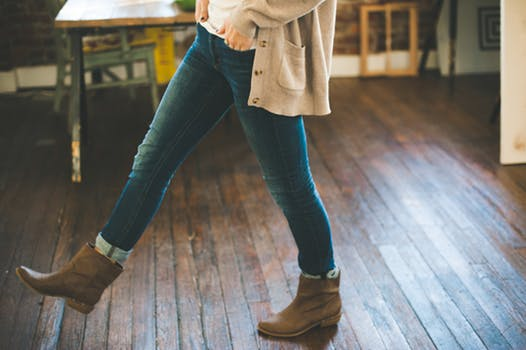 Girl in blue jeans wears brown boots with studs as she walks across a wooden floor.