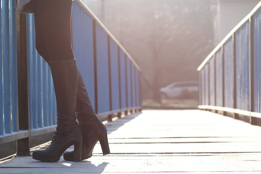 Female wearing long black boots with studs tucked into black jeans stands on a bridge.